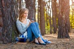 Das schöne blonde Mädchen, das im Wald stillsteht, sprechen durch Handy und und sitzen mit Tasse Tee und Buch Überzeugter Kaukasi Stockfoto