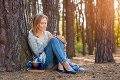 Das schöne blonde Mädchen, das im Wald stillsteht, sprechen durch Handy und und sitzen mit Tasse Tee und Buch Überzeugter Kaukasi Stockbilder