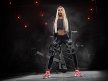 Das schöne blonde Mädchen, das Sport tut, trainiert in der Turnhalle, im Sport Lizenzfreies Stockbild