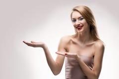 Das schöne blonde rote Lippenlächelnde Mädchen hält leeres Kopie spac Lizenzfreie Stockbilder