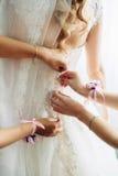 Das schöne Brauterhalten bereitete sich mit Brautjungfern auf dem Hintergrund eines Raumes vor Lizenzfreie Stockfotos