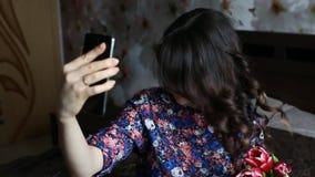 Das schöne Brunettemädchen, das selfie mit Rot tut, blüht Tulpen auf schwarzem smatfon stock footage