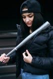 Das schöne Brunettemädchen mit einem Baseballschläger Lizenzfreie Stockfotos