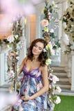 Das schöne Brunettemädchen, welches auf das Baby im purpurroten Kleid wartet, sitzen Lizenzfreie Stockfotos