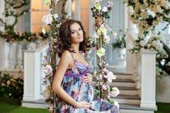 Das schöne Brunettemädchen, welches auf das Baby im purpurroten Kleid wartet, sitzen Stockbild