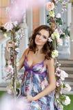 Das schöne Brunettemädchen, welches auf das Baby im purpurroten Kleid wartet, sitzen Stockfoto