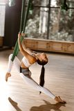 Das schöne dünne dunkelhaarige Mädchen, das in der weißer Sportspitze und -strumpfhosen gekleidet wird, tut, Übung auf grün stockfotos