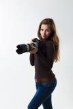 Das schöne Fotografmädchen mit Berufs-dslr Kamera, die auf einem weißen Hintergrund im Studio aufwirft Fotolernen Lizenzfreies Stockbild