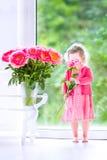 Das schöne gelockte Kleinkindmädchen, das mit Pfingstrose spielt, blüht Stockbild