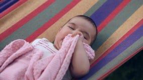 Das schöne glückliche kleine Mädchen, das in einer Hängematte im Garten liegt, lacht und zerfrisst Decke stock video footage