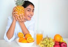 Das schöne indische Mädchen mit Früchten Stockfoto