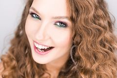 Das schöne junge blonde gelockte Mädchen, das im Studio mit Berufsmake-up aufwerfen und der offene Zahn lächeln Stockfoto