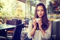 Das schöne junge Mädchen, das allein in einem Café sitzt, trinkt Kaffee Stockbilder