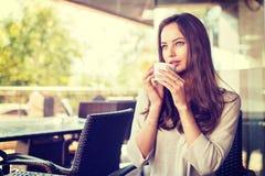 Das schöne junge Mädchen, das allein in einem Café sitzt, trinkt Kaffee Stockfotografie