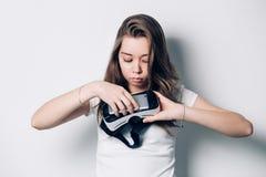 Das schöne junge Mädchen, das einen Kopfhörer der virtuellen Realität hält, setzt das Telefon, übertragen mit einem ernsten Gesic lizenzfreie stockfotografie