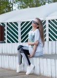 Das schöne junge Mädchen mit dem langen Haar in der Sonnenbrille sitzt an den weißen hölzernen Schritten Stockbild