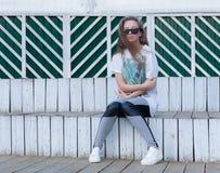 Das schöne junge Mädchen mit dem langen Haar in der Sonnenbrille sitzt an den weißen hölzernen Schritten Stockbilder