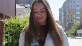Das schöne junge Mädchen schreibt eine Mitteilung, um einen Smartphone gehend hinunter die Straße im Sommer und im Lächeln zu ben stock video footage