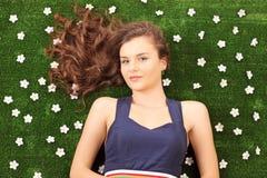 Das schöne junge weibliche Lügen auf einem Gras mit Gänseblümchen blüht stockbild
