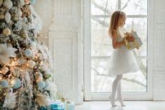 Das schöne kleine Mädchen, das an steht, geht am großen Fenster auf den Zehen lizenzfreies stockfoto