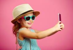 Das schöne kleine Mädchen, das im Sommerkleid, einen Strohhut und Sonnenbrille tragend gekleidet wird, macht ein selfie Porträt a stockbilder