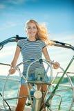 Das schöne Mädchen betreibt die Yacht Lizenzfreie Stockfotos