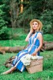 Das schöne Mädchen, das blaues Kleid tragen und der Hut sammeln Blumen im Korb im Holz Lizenzfreie Stockfotos
