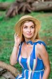 Das schöne Mädchen, das blaues Kleid tragen und der Hut sammeln Blumen im Korb im Holz Lizenzfreies Stockbild