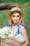 Das schöne Mädchen, das blaues Kleid tragen und der Hut sammeln Blumen im Korb im Holz Stockfotografie