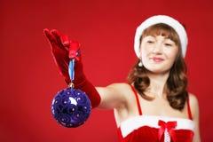 Das schöne Mädchen, das als Sankt gekleidet wird, hält ein Geschenk an. Stockbild