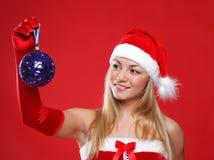 Das schöne Mädchen, das als Sankt gekleidet wird, hält ein Geschenk an. Lizenzfreies Stockbild