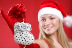 Das schöne Mädchen, das als Sankt gekleidet wird, hält ein Geschenk an. Stockbilder