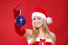 Das schöne Mädchen, das als Sankt gekleidet wird, hält ein Geschenk an. Lizenzfreie Stockbilder