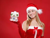 Das schöne Mädchen, das als Sankt gekleidet wird, hält ein Geschenk an. Lizenzfreie Stockfotografie