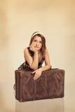 Das schöne Mädchen, das auf altem Koffer sich lehnt, tonte in der Retro Art lizenzfreies stockbild