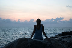 Das schöne Mädchen, das auf Steinen sitzt und in einem Abstand, das Mädchen bei Sonnenuntergang schaut, um in der Ruhe, schöner K Lizenzfreies Stockfoto