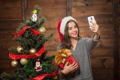 Das schöne Mädchen, das selfies macht, nähern sich Baum des neuen Jahres Stockfoto
