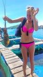 Das schöne Mädchen die Blondine der Tourist in einem rosa Badeanzug lizenzfreie stockbilder