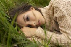 Das schöne Mädchen, das eine beige Strickjacke trägt, legt in eine Wiese unter Th stockbild