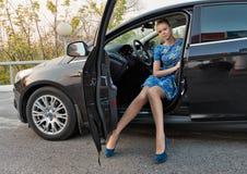 Das schöne Mädchen in einem blauen Kleid in einer Autokabine Stockfoto