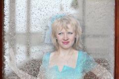 Schönes Mädchen in einem blauen Kleid hinter Glas Stockfotos