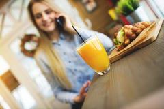 Das schöne Mädchen in einem modernen Café sprechend am Telefon, Fokus wird auf ein Glas des Safts und der süßen Oblate in Positio Stockfoto