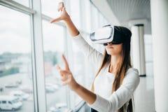 Das schöne Mädchen, das Gläser der virtuellen Realität verwendet, nähern sich hellem Fenster mit Wolkenkratzeransicht draußen Ges stockfoto
