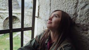 Das schöne Mädchen ist Sitzen oben am Fenster zugeschlossen mit Stangen und traurig stock video footage