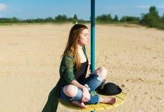 Das schöne Mädchen meditiert auf dem Strand Stockfoto