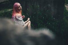 Das schöne Mädchen mit dem rosa Haar sitzt auf der geworfenen Leiter in einer Umwelt eines grünen Grases Stockfoto