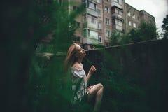 Das schöne Mädchen mit dem rosa Haar sitzt auf der geworfenen Leiter in einer Umwelt eines grünen Grases Stockfotos