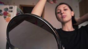 Das schöne Mädchen schaut in einem Spiegel und kämmt das Haar mit ihren Händen, a bildet stock video footage