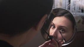Das schöne Mädchen schaut in einem Spiegel und malt die Augenbrauen mit einem Bleistift, a bildet stock footage