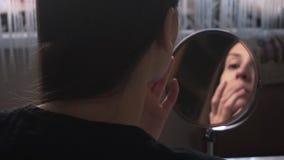 Das schöne Mädchen schaut in einem Spiegel und wendet Abdeckstift an der Haut, a bildet an stock video footage